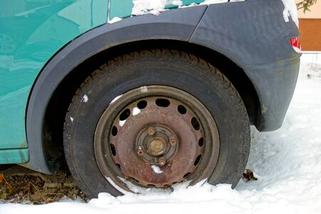Wheel of an old car in the snow
