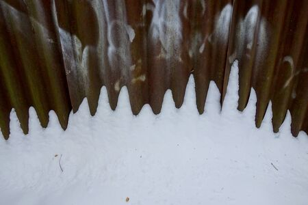 Corroded fence in the snow