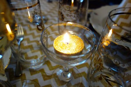 Gilt burning candle in a glass