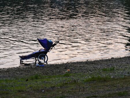 Wheelchair on coast of lake with disabled boy