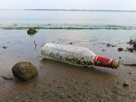 Abandoned glass bottle on sandy beach