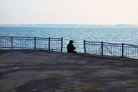A lone fisherman fishing in a harbor Banque d'images