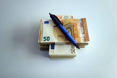 The official pen used in the financial sector lies on the banknotes Foto de archivo