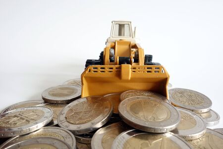 Bulldozer piling up euro coin. The photo shows the accumulation of money in the financial sector 写真素材 - 137666114