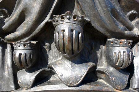 Escultura de acero fundido con tres cabezas de reyes con armadura militar.