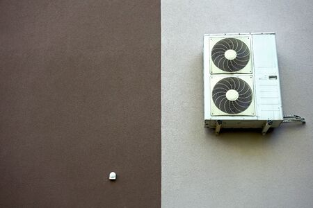 Air conditioner attached to the insulated wall of the building