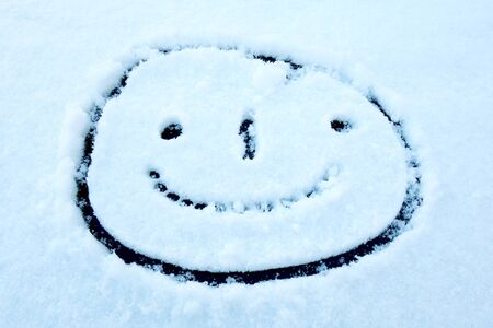 Drawn smiling face in snow on glass