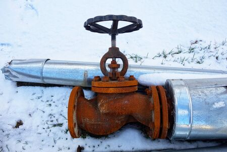 Discarded old insulated hot water pipe with valve on snow 写真素材