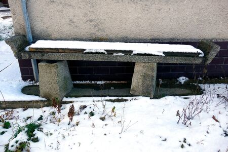 Abandoned and damaged bench covered with snow in winter near the building
