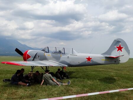 Poprad, Slovakia - JULY 29, 2014Parking military aircraft YAK- 52 on grassy plane airport on air show.