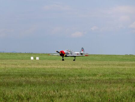 Poprad, Slovakia - JULY 29, 2014: Starting military aircraft YAK- 52 on grassy surface airport on air display.