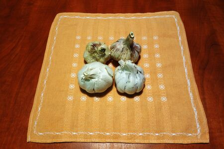 Raw garlic on tablecloth on kitchen table