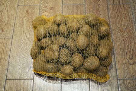Fresh potatoes packed in a net 写真素材