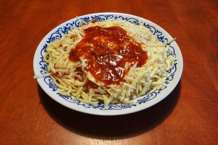 Spaghetti with tomato sauce and grated cheese