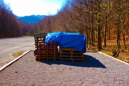 Stacked wooden pallets on a gravel bed covered with a blue waterproof tarpaulin
