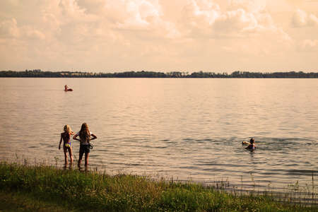 Girls are playing and swimming in the lake during the holidays at the summer resort