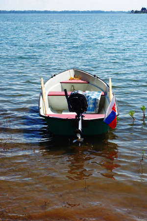 A small motor boat on the shore of a recreation center in summer
