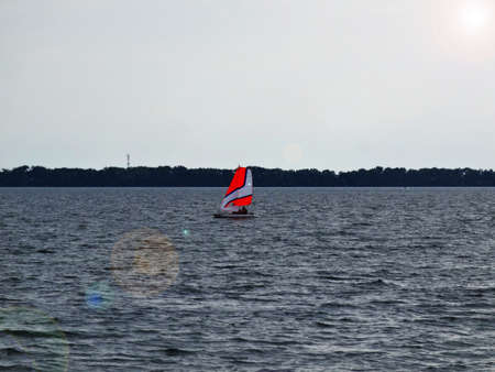 Sailboat with patterned sails on the lake on a sunny day