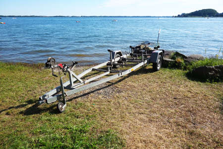 Abandoned boat trailer on the shore of a lake beach in summer season