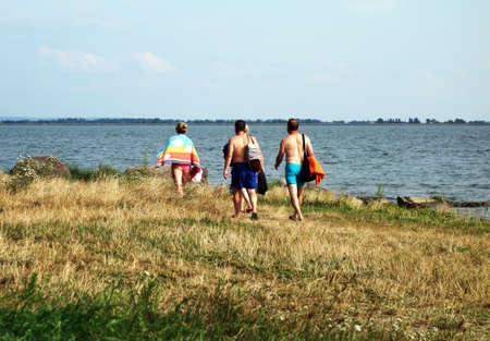 Group of young people walking along the beach of a lake in summer