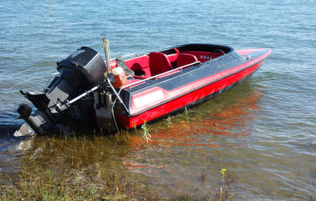 Fast small motor boat on the shore of the lake Stock Photo