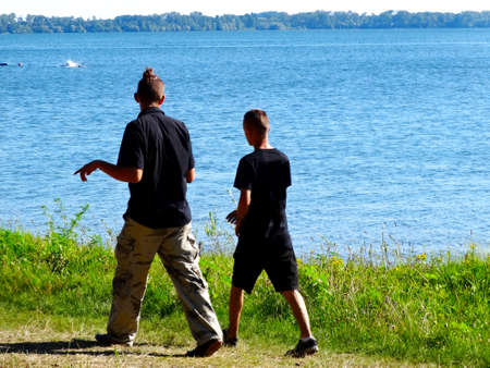 Young boys walking on the sidewalk on the beach by the lake in summer 写真素材