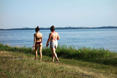 Young women walking on the grassy beach of the lake in a swimsuit 写真素材