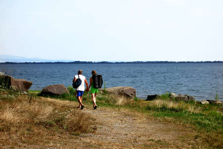 Man and woman on a walk along the grassy beach by the lake in August
