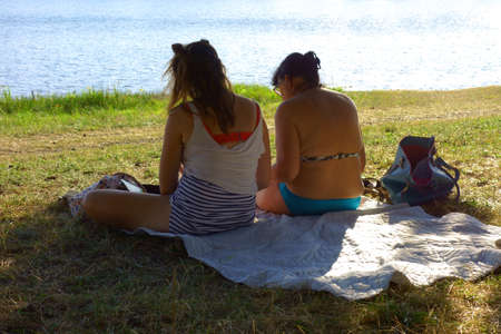 A mother and daughter sit on a blanket by the lake during a beautiful sunny day 写真素材