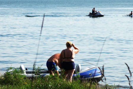 Man and woman board a rubber boat on the beach at a resort in summer