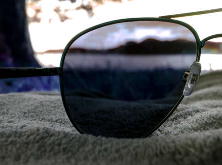 Sunglasses on a blanket on a grassy beach