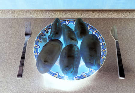 Inverted carp bladders on a kitchen counter with cutlery