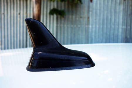 A black car antenna on the white roof of a car that receives radio waves