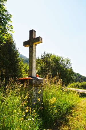 Christian cross on a concrete pedestal by the road in nature