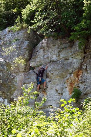 A climber climbs a travertine wall in Dreveník Slovakia 免版税图像