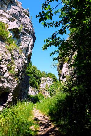 Hiking trail passes between travertine rocks, Dreveník Slovakia