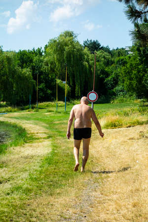 A man in a swimsuit walks across the grass by a lake in the summer season