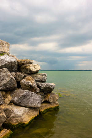 View of the lake with a rocky wall on the right, storm clouds approaching in the background 免版税图像