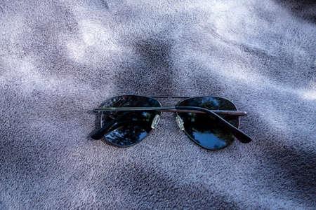 Deferred sunglasses on beach blanket near the lake