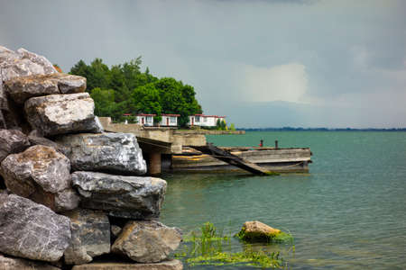 Harbor pier made of concrete and wood on the lake by a wall of stone, in the background above the horizon are active storm clouds 免版税图像
