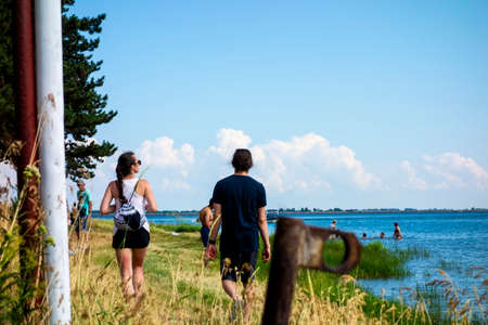 A young couple walks along a grassy beach by the lake on a beautiful summer day 免版税图像