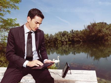 ady: Beautiful young businessman using laptop outdoors  Stock Photo