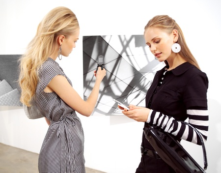 girl-friend with mobile phones at an exhibition  photo