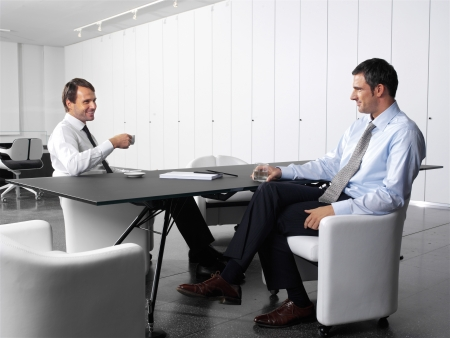 dinner wear: businesspeople having a business meeting at coffee table in office lobby