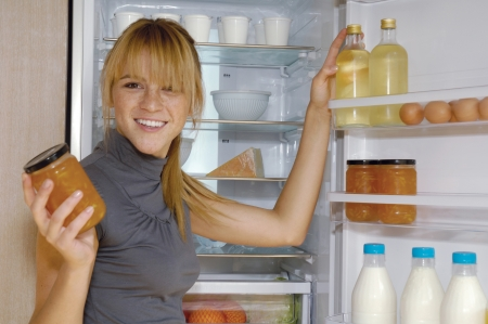 Mature woman looking for something in the fridge at home  Reklamní fotografie