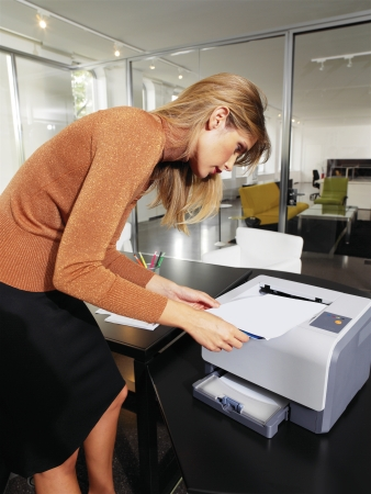 copy machine: business woman with documents standing next to printer Stock Photo