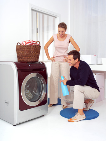 Man puts clothes into the washing machine while woman smiling