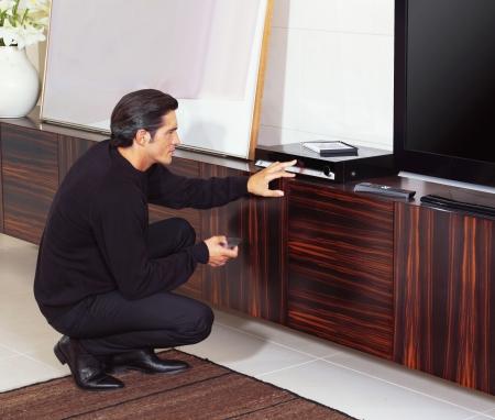 man using dvd player in living room Reklamní fotografie