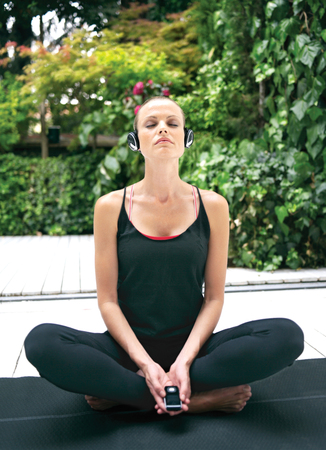 natural energy: Beautiful young woman in earphones doing yoga exercise outdoors