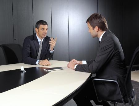 poner atencion: Dos empresarios discutir tareas sentado en la mesa de la oficina